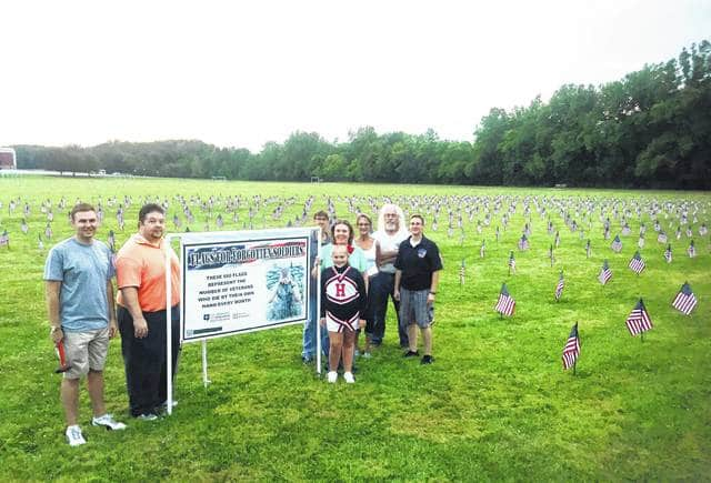 Volunteers with Support Our Troops of Highland County are shown just after planting 660 flags at Southern State Community College on Wednesday evening.