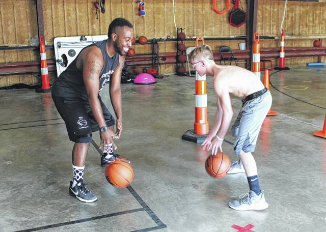 Tirrell Cumberland, left, dribbles with Logan Bieler at the old Warren Furniture warehouse on Muntz Street Friday afternoon. Bieler is a Hillsboro Christian Academy student from Winchester.