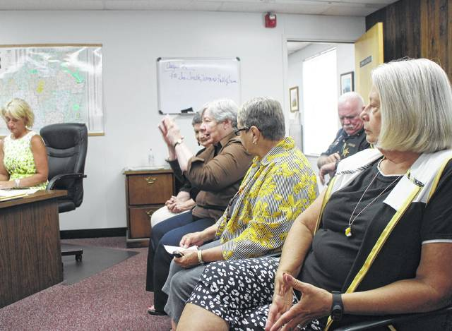 Representatives of the Highland County Women's Hall of Fame, including 2017 inductee Karen Faust, foreground, speak to the Highland County Board of Commissioners on Wednesday.