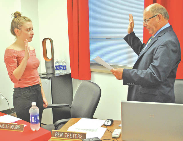 Senior Isabelle Bourne, left, was sworn in Monday as the new student representative to the Hillsboro City Schools Board of Education. Swearing her in is treasurer Ben Teeters.