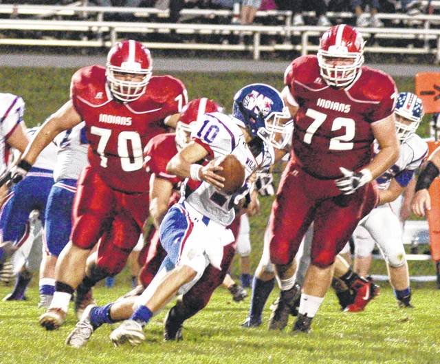 Max Conover tackles the WillIamsburg Wildcats QB in the backfield as Draven Stodgel and R. J. Swackhamer give chase on Friday night in Hillsboro.