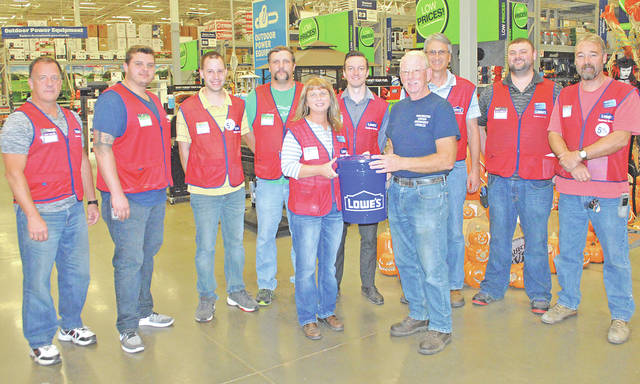 Pastor Greg Roberts is pictured with the Hillsboro Lowe's management team and one of the 100 five-gallon buckets filled with supplies the store partially donated to help hurricane victims. Standing directly behind Roberts is Lowe's store manager Roger Bowlby.