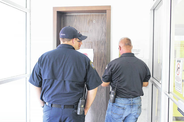 Paint Creek Joint EMS/Fire District interim chief Dave Manning, right, works on an elevator control at an uptown office building Thursday afternoon. A man was stuck inside for about 35 minutes while crews responded.