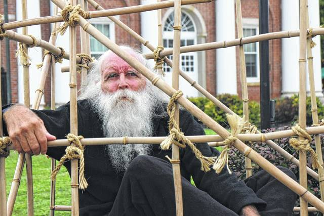 "Ron Wernke, a Vietnam War veteran and member of the Vietnam Veterans Motorcycle Club of Ohio, sits in a bamboo cage on the front lawn of the Highland County Courthouse on Friday. Wernke, also known as ""ZZ,"" sat in the cage as a memorial to prisoners of war and members of the military declared missing in action."