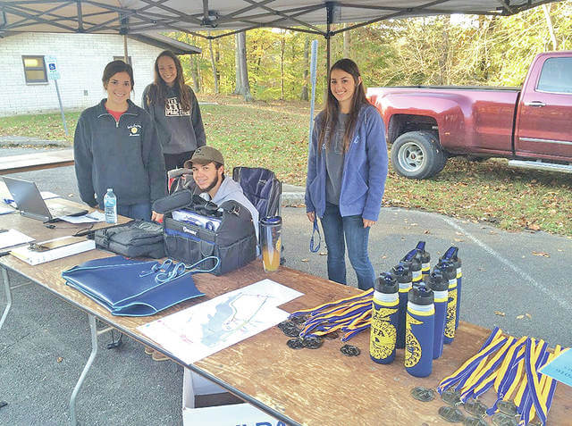 The Hillsboro FFA will hold the the annual Adopt-A-Family 5K on Saturday, Oct. 21 at the Rocky Fork State Park, 9800 North Shore Dr. Preregistration is $20 and includes a free T-shirt. Registration forms are available in the Hillsboro High School main office or by contacting the Hillsboro Ag Department at 937-393-3485, ext. 1582. Day of registration is available at 8 a.m. and the race starts at 9 a.m. All proceeds will be used to benefit families in need around Highland County during the holiday season. The top male and female for each age division will be awarded. New this year, runners can also dress up in costumes, and prizes will be given for the best costumes. Last year 91 runners and walkers participated in the race. The FFA hopes to have an even bigger turnout this year. Pictured, from left, are Breanne Fender, Taylor Chaney, Kaleb Harp and Mackenzie Oglesby working at the registration table during the 2016 Hillsboro FFA 5K.