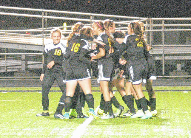 Lady Mustangs surround Riley Creditt to celebrate her goal late in the second half of Lynchburg-Clay's regional semi-final victory over Wheelersburg.
