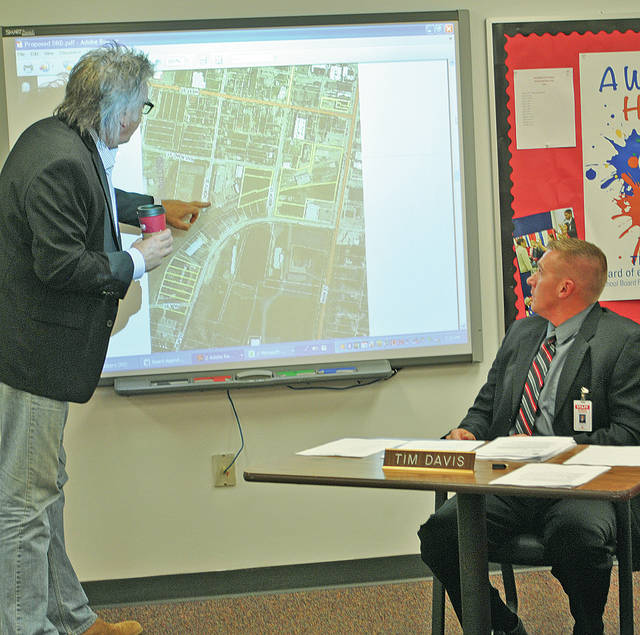Hillsboro Mayor Drew Hastings, left, shows the Hillsboro Board of Education a map of a proposed Downtown Redevelopment District while superintendent Tim Davis looks on.