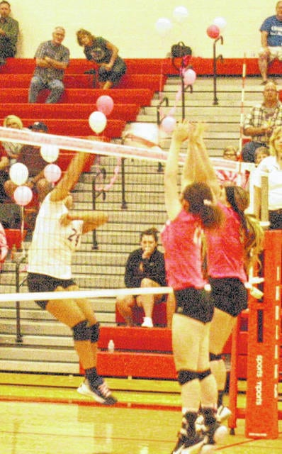 "Two Lady Indians block a spike attempt by the Lady Cavaliers on Tuesday at Hillsboro High School in the Lady Indians ""Volley for the Cure"" game."
