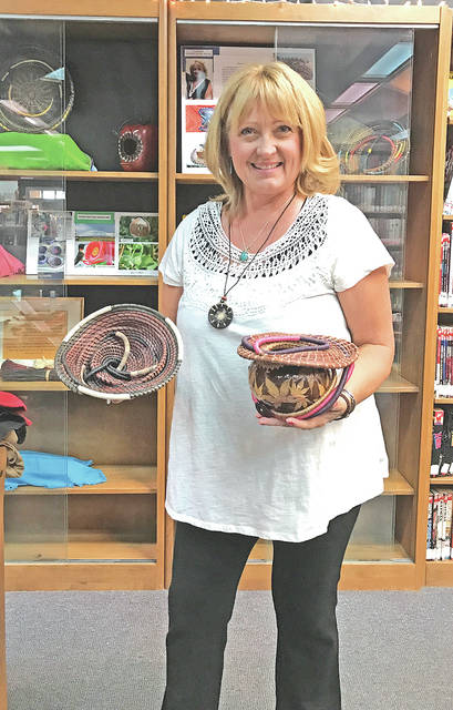 Patty Hubler is pictured with her gourd and pine needle crafts at the Hillsboro library.
