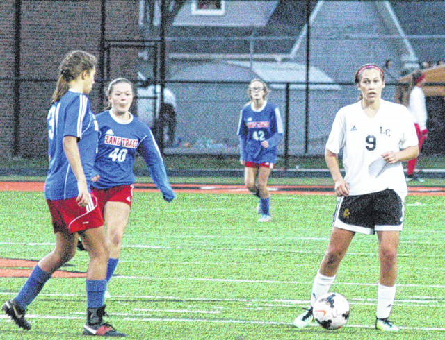 Peyton Scott surveys the field as two Lady Pioneer defenders converge on her Wednesday at Waverly High School during the Lady Mustangs district semi-final match.
