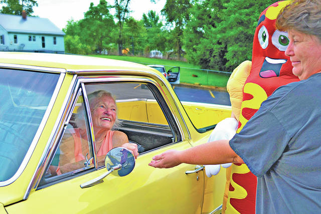 Eloise Garrison (driving), Mr. Hotdog and Rhonda Purdin, the Highland County Senior Citizen Center director of foods and banquets, display what it looks like to pick up lunch during one of the center's Wednesday drive through events.