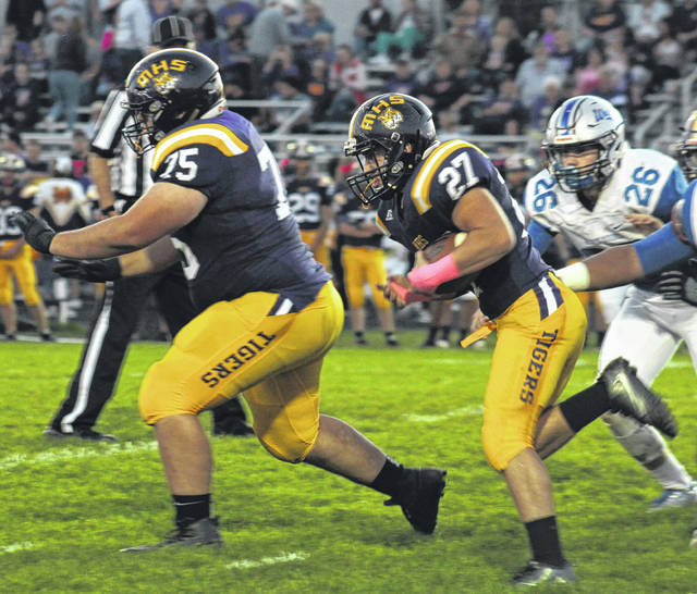 Tanner Tite runs behind Trevor Tite on Friday at McClain High School against the visiting Washington Blue Lions.