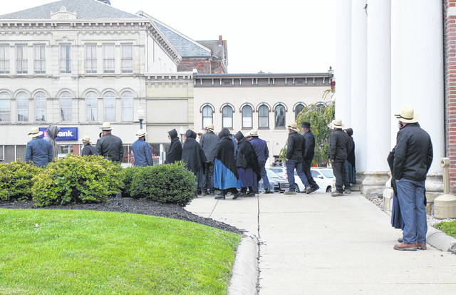 A gathering of residents, including many members of the Amish community, exit the Highland County Courthouse Monday after a hearing involving a local Amish family.