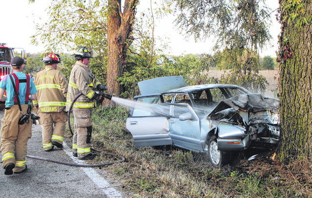Firefighters soak a partially burned vehicle Tuesday evening on SR 753 north of Greenfield.