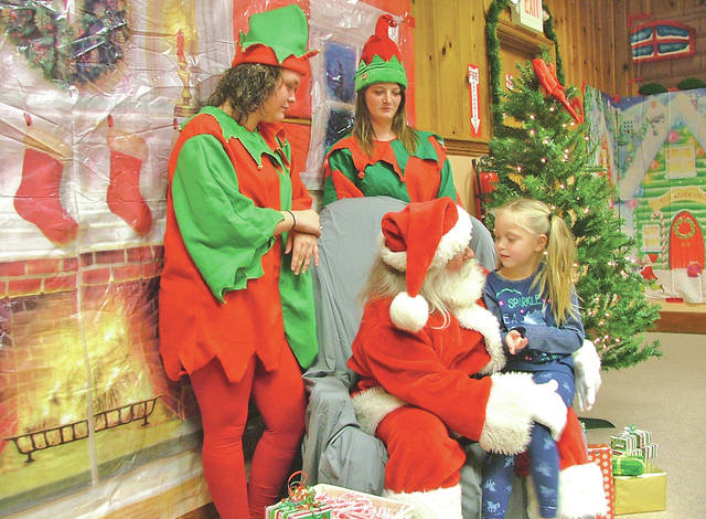 Natalee Pullin talks with Santa Claus and his helpers during part of a Hillsboro Uptown Business Association Christmas event held a year ago at The Times-Gazette offices. Pullin, 5 years old at the time, told Santa she wanted a Barbie Dream House for Christmas.