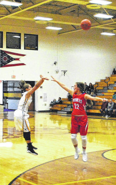 Emma Stegbauer shoots a three as a Lady Indian defender challenges on Saturday at McClain High School during a foundation game for the memorial of John Wend.