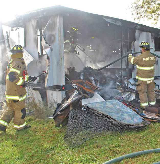 Firefighters battle the remnants of a fire Wednesday that destroyed a trailer on Heathermoor Trail in the Rocky Fork Lake area.
