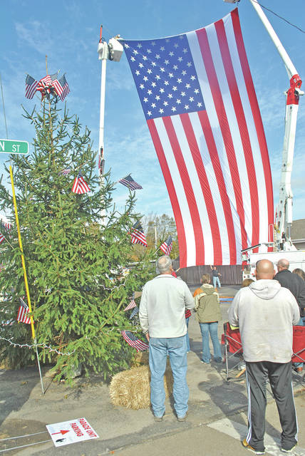 "A pair of AEP bucket trucks lift a large United States flag into place Saturday during a celebration in Bainbridge saluting RFD-TV's ""Best Of America By Horseback"" taping a pair of Christmas-themed patriotic shows Saturday and Sunday at the Paxton Theatre. A short program and parade followed the raising of the flag and an estimated 1,000 flags lined entrances to the town on U.S. Route 50. During the program preceding the parade, and with Veterans Day approaching on Nov. 11, Highland County Veterans Service Commission Vice President Kevin Barreras told the crowd, ""Veterans shouldn't honor themselves, they should be honored by the community, and my hat's off to Bainbridge for doing that."""
