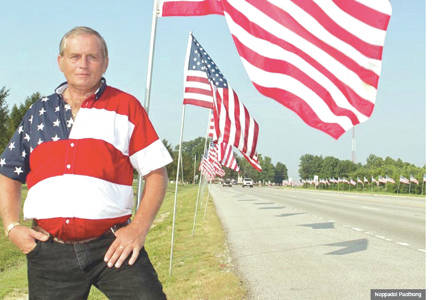 """Larry """"The Flagman"""" Eckhardt is pictured with one of his displays similar to the one he will place along U.S. Route 50 heading into Bainbridge on Saturday."""
