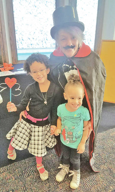 Greenfield Library Branch Manager Sharon Aukeman is pictured with Kallista and Kariana Hennison as they discuss the magic of books during story time at the library.