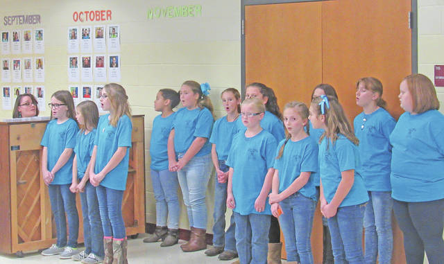 "Elementary music teacher Vicki Mikkelson (at the piano) leads fifth-grade honor choir members in a performance of ""All Things Bright and Beautiful"" at Monday's Greenfield Exempted Schools Board of Education meeting."