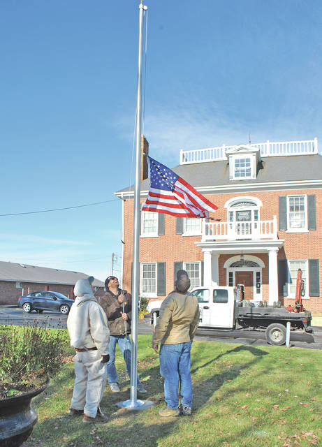 From left, Vernon Garrison and Justin Harsha and John Willis of the Harsha Monument Company watch Tuesday as a flag is raised on a new pole in front of the Scott House in Hillsboro for the first time.