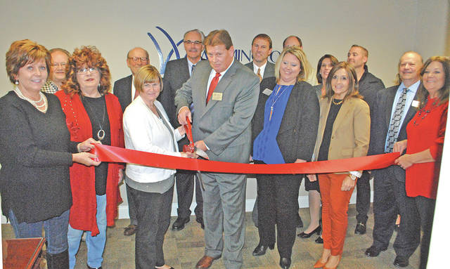 Tim Priest, vice president of lending, prepares to the cut the ribbon during a grand opening ceremony Friday at the new Hillsboro office of Wilmington Savings Bank, located at 137 N. High St., Suite 201. Office hours are 9 a.m. to 5 p.m. Monday through Friday. Pictured with Priest are members of the Highland County Chamber of Commerce, other bank officials and community members.
