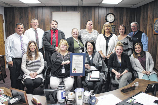 The Highland County Commissioners pause for a photo on Wednesday with caseworkers and other Children Services officials at a commissioners meeting. The board issued a proclamation declaring the month of November Adoption Month in Highland County.