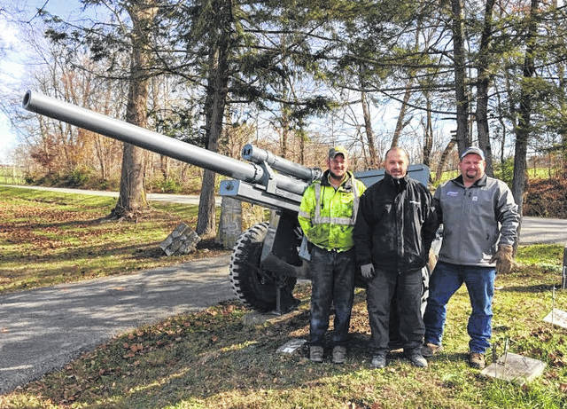 From left, Kenny Butler and Todd Wilkin of Best One Tire, and Jamie Reed of Coyote Manufacturing stand with the newly refurbished cannon at the Hillsboro Cemetery.