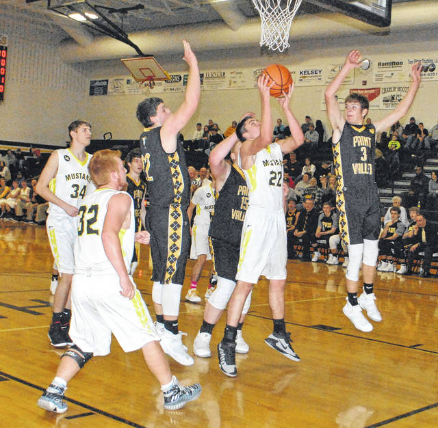 Raymond Connor (#22) attempts an up and under move on Friday at Lynchburg-Clay High School as he is surrounded by three Paint Valley defenders.