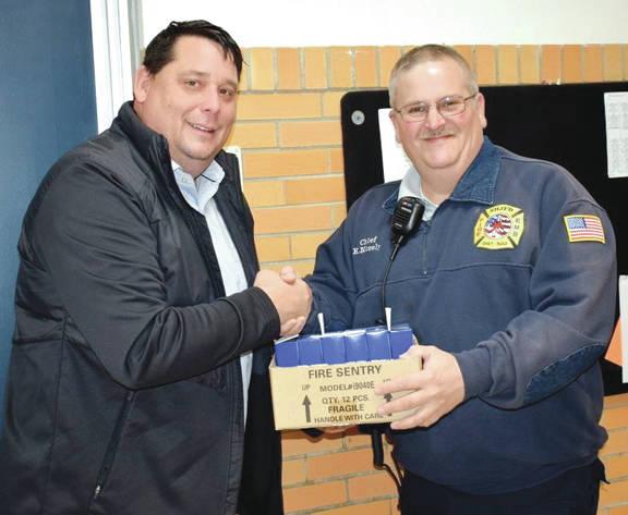 Southern Highland Joint Fire District Chief Kevin Mosley, right, presents smoke detectors to Whiteoak High School Principal Brian Ruckel.