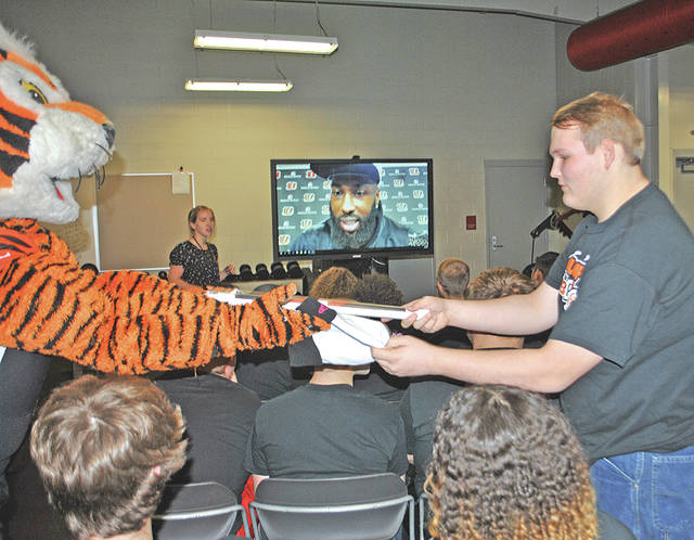 Hillsboro High School student Brian Midkiff receives a tobaggan and poster from Who Dey, the Cincinnati Bengals mascot. In the background, Bengals wide receiver Brandon LaFell is shown participating in a live Skype session with Hillsboro students.