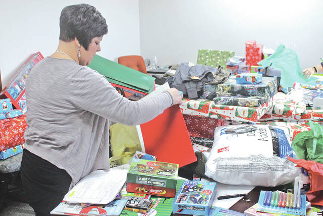 Tara Smith Decker of the Highland County Prosecutor's Office prepares gifts for local children in the grand jury room at the prosecutor's office.