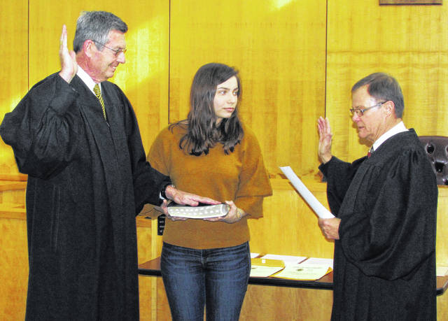David McKenna, left, was sworn-in for a fourth term as Hillsboro Municipal Court judge on Thursday by Highland County Common Pleas Judge Rocky Coss, right. McKenna was re-elected in November, running unopposed. His daughter, Ali, is shown holding a Bible as her father is administered the oath during ceremonies at the municipal courtroom.