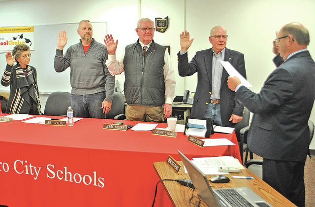 Hillsboro Board of Education members were sworn in during an organizational meeting Monday night by treasurer Ben Teeters, right. The board members being sworn are, from left, Beverly Rhoads, Bill Myers, Jerry Walker and Larry Lyons. Rhoads, Myers and Lyons were had already been serving on the board, while Walker is a former board member who was elected again in November. The other board member is Tom Milbery.