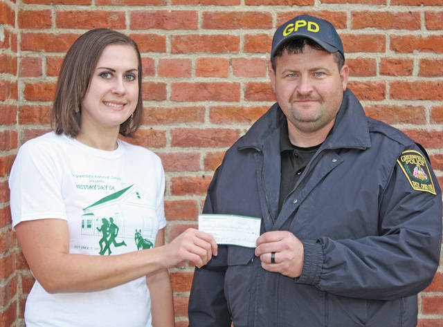 The Greenfield Historical Society Board of Directors recently voted to donate a percentage of the proceeds from its History Day 5K Run Walk to the Greenfield Police Department toward the purchase of a new police dog. In the photo, board member and 5K organizer Wendy Ellis presents a check for $500 to Greenfield Police Chief Jeremiah Oyer. The police department has collected donations over the past year and is nearing its goal with less than $3,000 left to go. The society's board wanted to thank the department for all it does for the Greenfield community.