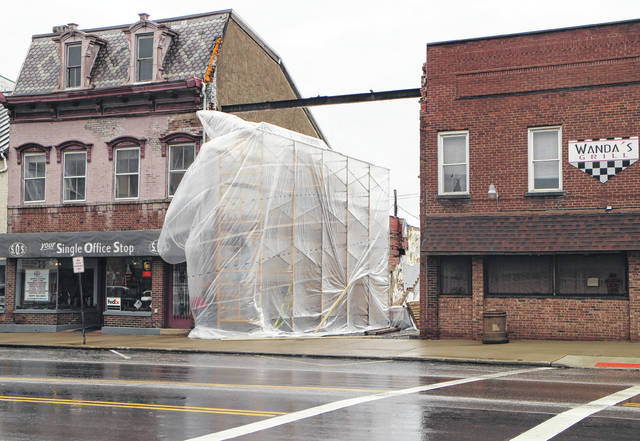 A large plastic cover flaps in the wind on Thursday, covering scaffolding in the former Colony Theatre space that will be used in the construction of a brick wall covering the exposed side of the Single Office Stop building.
