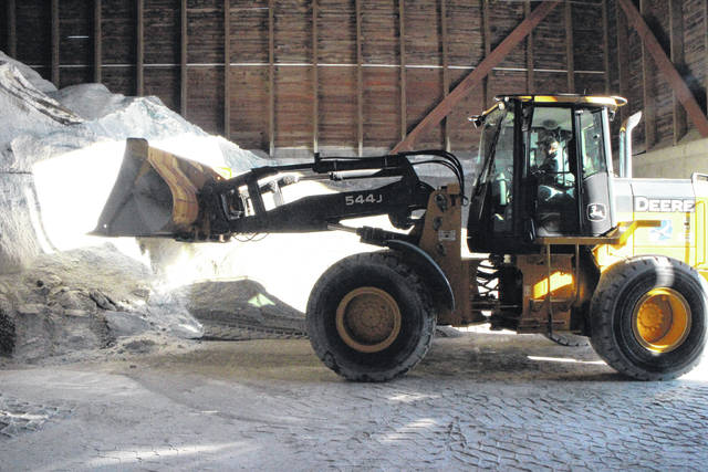 Foreman Mike Truman of the Highland County Engineer's Office uses a frontloader Tuesday afternoon to scoop a mixture of salt and limestone grit at the county garage.