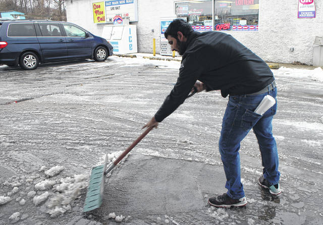 TJ Patel shovels slush Monday afternoon in the parking at the Sunoco on SR 124 in Hillsboro. Patel, whose family owns the gas station, said he was visiting from Illinois.