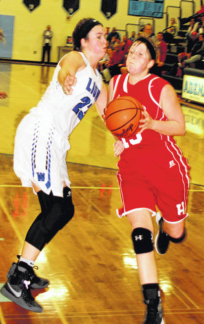 Lana Grover of Hillsboro drives against Shawna Conger of Washington on Thursday at Adena High School as the two teams battled in the Division II girls sectional basketball tournament.