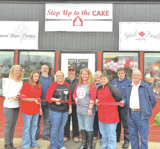 Pictured in front of Step Up to the Cake in Leesburg are (back row, l-r) Leesburg Village Council members Scott Willey, Chris Runyon, Shawn Priest and John Michael; (front row, l-r) Tracy Evans with Grow! Highland County, Jamie Sheppard, Casey McIntosh, Summer Howard, Teal McFerron and Leesburg Mayor Freddie Snyder.
