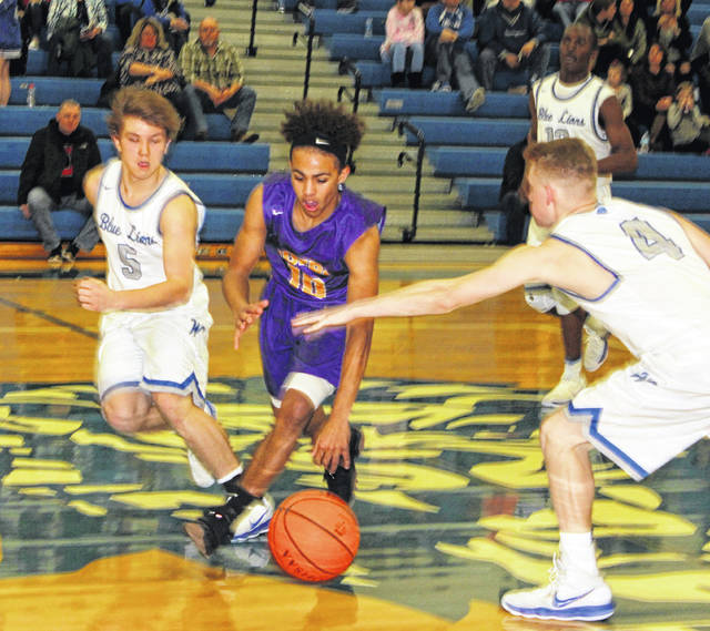 McClain's Kobe Penwell splits two Blue Lions defenders at mid-court on Friday at Washington High School in Washington Court House.
