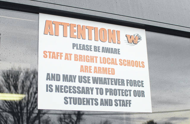 "This sign is posted in the doorways of Whiteoak Jr./Sr. High School and Bright Elementary School. It reads, ""Attention! Please be aware staff at Bright Local Schools are armed and may use whatever force is necessary to protect our students and staff."""