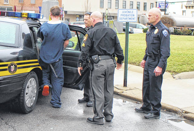 Thomas Barney, left, steps into a sheriff's cruiser Wednesday afternoon outside the Highland County Courthouse following a hearing. Shown at the door are Deputy Chet Gibson and Sgt. Danny Croy of the Highland County Sheriff's Office and Hillsboro Police Chief Darrin Goudy, far right.