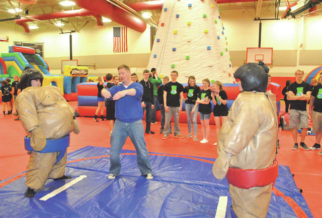 """Former volunteer Adam McGinnis, center, gives directions before a pair of """"sumo"""" wrestlers square off during a past Hillsboro After Prom Party."""