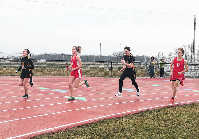Boys and girls from Fairfield and Lynchburg-Clay compete at the same time in the 4x800-meter relay on Monday at Fairfield High School. Pictured (l-r): Emily Pinkerton, Morgan Richmond, Dawson Osborn and Matthew Mangus.