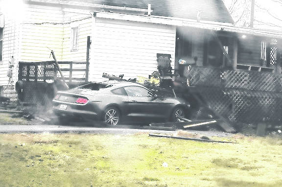 A Ford Mustang is pictured Thursday afternoon after it struck a home in the 100 block of North Second Street in Greenfield.