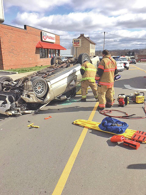 Paint Creek Joint EMS/Fire District personnel work to extricate a man from the scene of a one-car accident Friday on Jefferson Street in Greenfield.