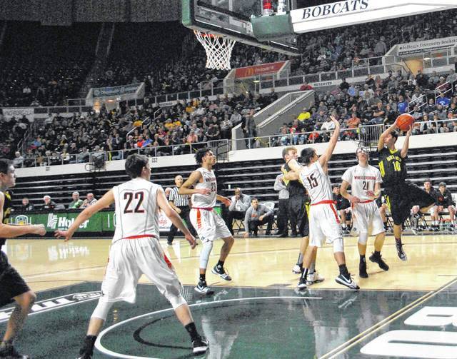 Lynchburg-Clay's Damin Pierson leaves his feet to make a pass while fellow Mustang Eric McLaughlin battles for position in the post on Saturday, at the Convocation Center on the campus of Ohio University, as the Mustangs battled the Wheelersburg Pirates in the Division IV District Semi-Final game.