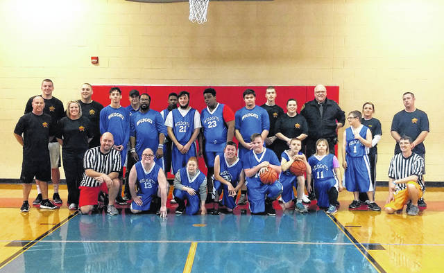 The Highland County Special Olympics Wildcats basketball team and the Highland County Sheriff's Office basketball team pose for a picture before their game on Friday at the Hillsboro YMCA. Back row (l-r): Deputy Bates, Deputy Young, Coach Phil Louden and Malik Rutledge, Deputy Myers, Sheriff Donnie Barrera, Deputy Engle and Deputy Conrad. Middle row (l-r): Danny Croy, Jennifer Schinkal, Darius Mustard, Terrell Willis, Jordan Humphrey, Amiri Harewood, Josh Lomangino, Deputy Stanley, Christian White and Event Director at Hillsboro YMCA Chris Tracy. Front row (l-r): Highland County Special Olympics Coordinator Nathan Boatman, Randy Heaton, Letitia Couch, Brandon Evans, Harrison Grove, Matthew Adams and Courtney Adams.